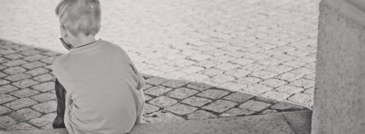 garoto triste de costas pensando